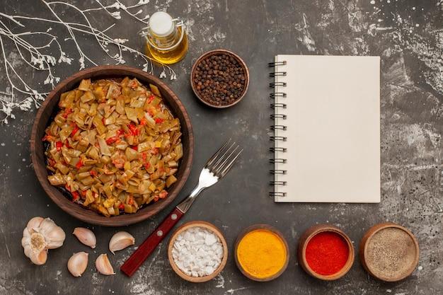 Plat appétissant haricots verts dans l'assiette à côté de la fourchette à l'ail bouteille d'huile cahier blanc et bols d'épices sur la table sombre