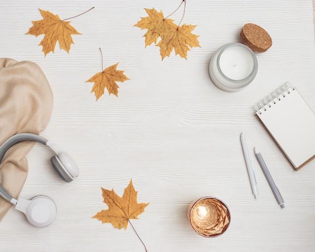Plat d'automne détente à la maison avec ordinateur portable et casque verre d'eau bougie aromatique sur bois