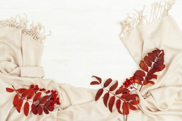 Plat à l'automne avec des feuilles de sorbier de couleur rouge et de sorbier sur une écharpe féminine automnale douce sur un fond en bois blanc avec copie vue de dessus.