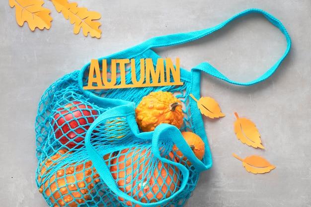 Plat à l'automne avec un sac à cordes turquoise avec des citrouilles orange, le haut vie sur pierre grise