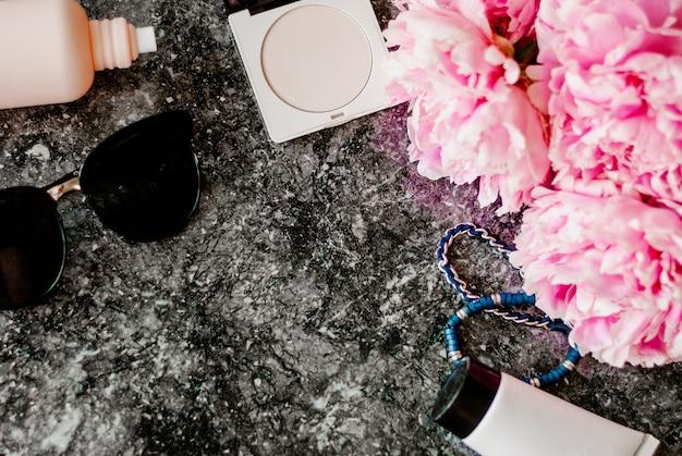 Plat de beauté avec accessoires, parfums, cosmétiques et pivoines sur fond de marbre foncé