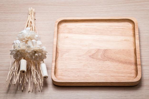 Plat en bois avec fleur séchée sur la table en bois.