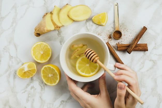 Plat de boisson saine au citron, racine de gingembre frais, bâtons de cannelle et sirop d'agave sur fond de marbre, rhume naturel ou mal de gorge