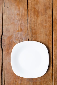 Plat carré en céramique blanche sur la table en bois vintage