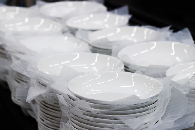 Plat en céramique blanche avec du papier dans des ustensiles de cuisine