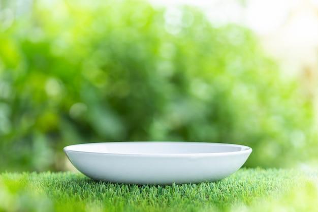 Plat en céramique vide blanc sur une table en bois avec vert flou fond clair. pour montage photo