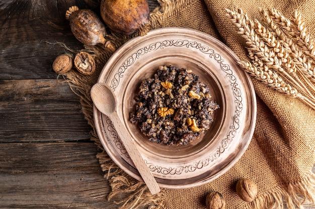 Plat de céréales de cérémonie kutia avec du miel, des raisins secs et des graines de pavot. repas traditionnel la veille de noël. bannière, menu, lieu de recette pour le texte, vue de dessus.
