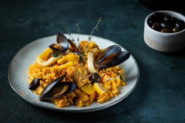 Plat classique d'espagne, paella de fruits de mer en assiette sur fond bleu vue de dessus. paella espagnole aux crevettes, pinces, moules et citron frais. nourriture espagnole. nourriture de confort. riz aux fruits de mer.