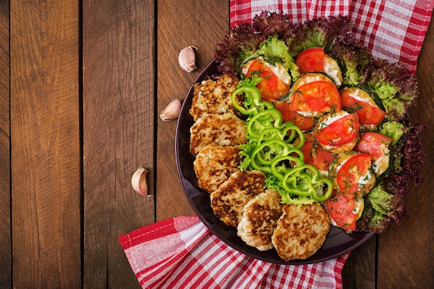 Plat avec une collation de courgettes frites aux tomates et de succulentes escalopes de poulet aux courgettes. vue de dessus