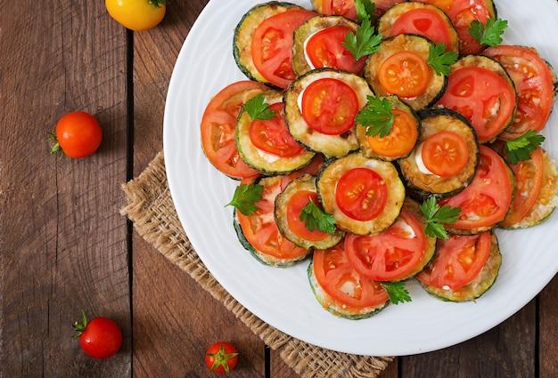 Plat avec une collation de courgettes frites aux tomates. vue de dessus