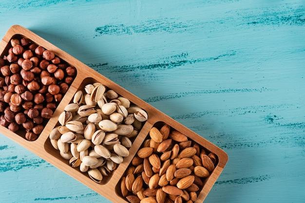 Plat compartimenté avec des noix sur une table en bois bleue. noisette, amande, pistache.