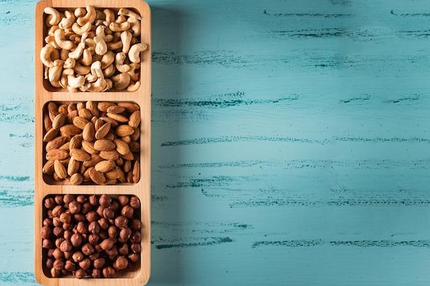 Plat compartimenté avec des noix sur une table en bois bleue. noix de cajou, noisette, amande.