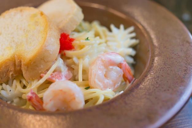 Plat de crevettes spaghetti carbonara sur fond de bois, fruits de mer crémeux au pesto
