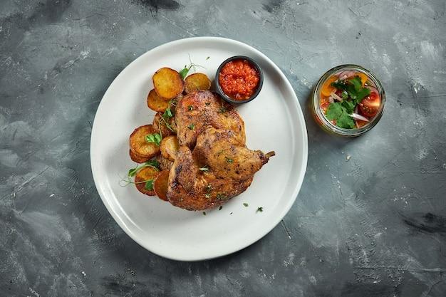 Plat de cuisine géorgienne poulet tapaka ou tabaka sur une assiette, sur une surface en bois