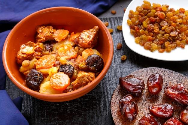 Plat de cuisine juive douce zimmes avec des dates, des carottes et de la viande de dinde dans une assiette brune sur un tableau noir sur une surface bleue près de raisins secs et de dates