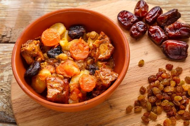 Plat de cuisine juive douce zimmes avec dates, carottes et viande de dinde dans une assiette brune sur un tableau noir