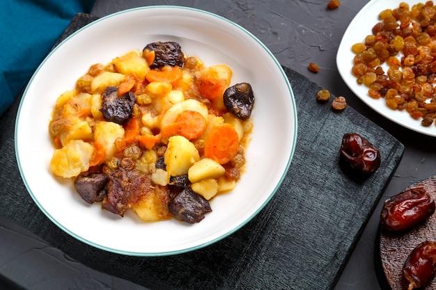 Plat de cuisine juive douce zimmes avec dattes végétariennes carottes dans une assiette sur une surface en béton sur un tableau noir