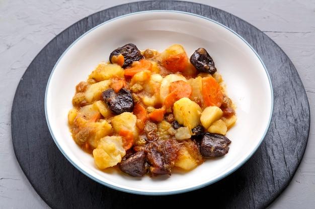 Plat de cuisine juive douce zimmes avec dattes végétariennes carottes dans une assiette sur une surface en béton