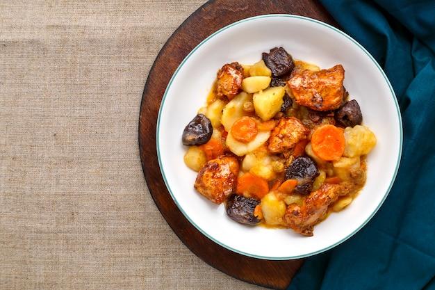 Plat de cuisine juive sweet tsimes avec carottes, dattes et viande de dinde dans une assiette blanche sur une planche ronde sur une surface en lin