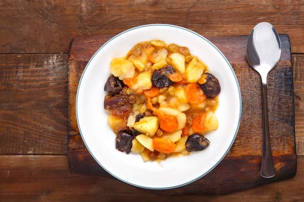 Un plat de cuisine juive tsimes avec des carottes et des dattes dans une assiette blanche sur une planche de bois à côté d'une cuillère