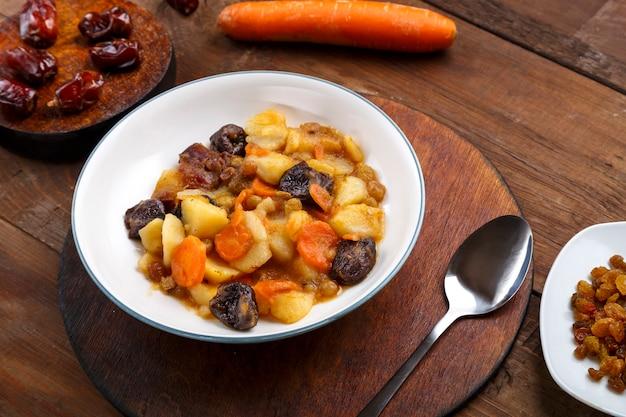 Un plat de cuisine juive tsimes avec des carottes et des dattes dans une assiette blanche sur un support rond à côté d'une cuillère de carottes