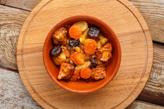 Un plat de cuisine juive tsimes avec carottes, dattes et viande de dinde dans une assiette en argile sur un support rond en bois