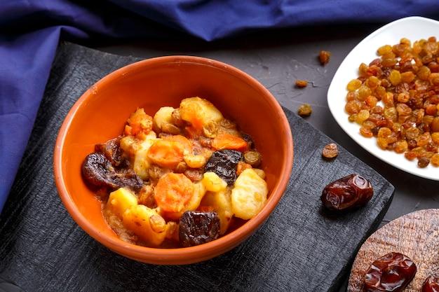 Plat de cuisine juive tsimes sucrés aux dattes de carottes végétariennes dans une assiette sur une surface en béton avec une serviette bleue