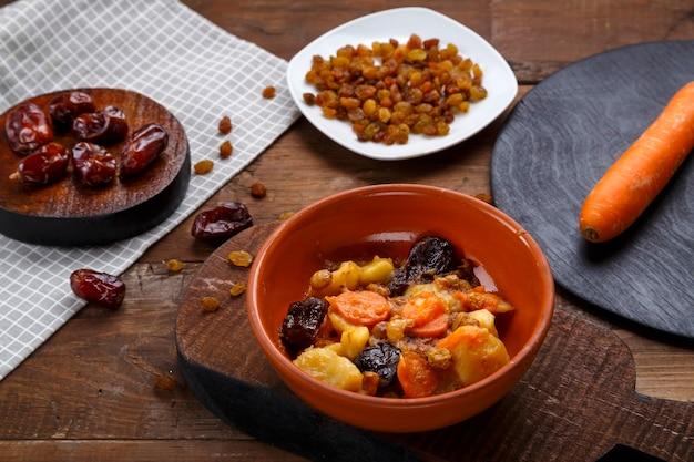 Un plat de la cuisine juive tsimes sucrés avec des carottes aux dates dans une assiette à côté d'une cuillère et des carottes aux fruits secs