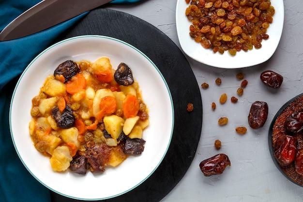 Un plat de cuisine juive tsimes sucrés avec des carottes dattes végétariennes dans une assiette sur un support rond sur une surface en béton près de dates raisins secs