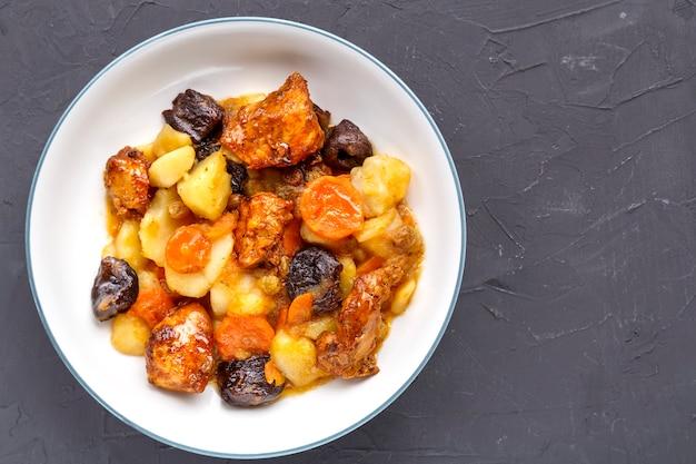 Un plat de cuisine juive tsimes sucrés avec des carottes, des dattes et de la viande de dinde dans une assiette blanche sur une surface en béton