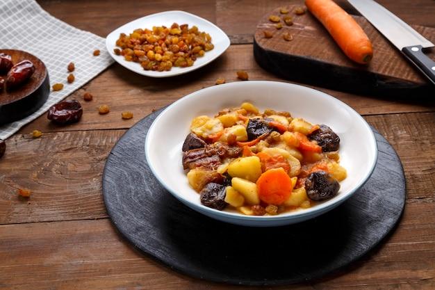 Plat de cuisine juive tsimes sucrés avec des dates de carottes végétariennes dans une assiette d'argile sur une planche de bois près de fruits confits