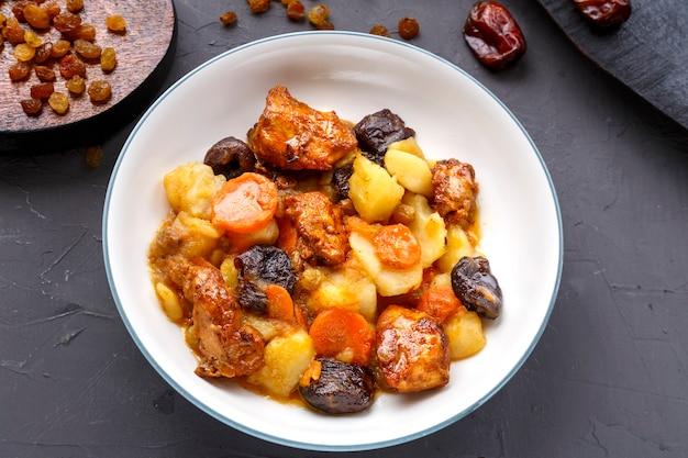 Plat de cuisine juive tsimes sucrés avec des dates, des carottes et de la viande de dinde dans une assiette blanche sur un tableau noir sur une surface en béton près des raisins secs et des dates