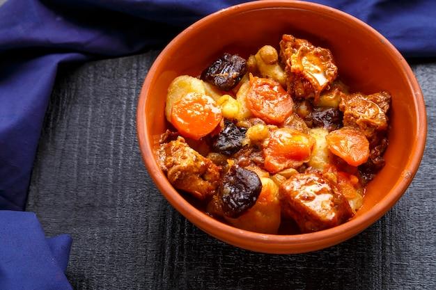 Plat de cuisine juive tsimes sucrés avec des dates, des carottes et de la viande de dinde dans une assiette brune sur une surface bleue