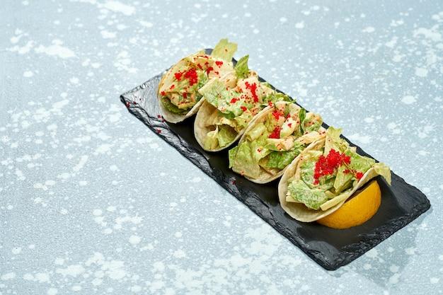 Plat de cuisine mexicaine - tacos au saumon, laitue, sauce blanche et caviar tobiko sur une plaque noire sur fond bleu