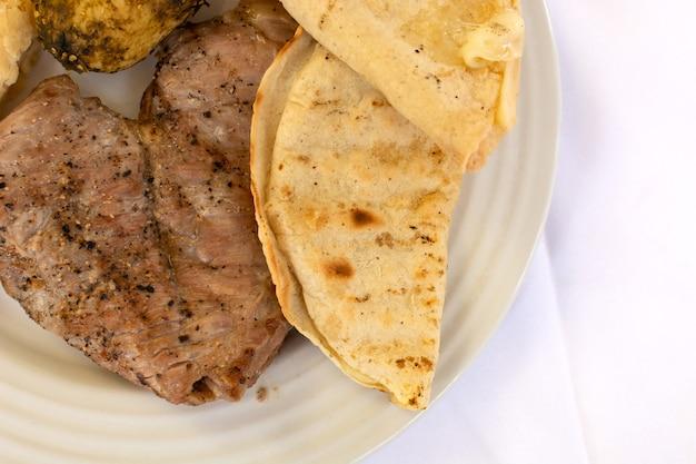 Plat de cuisine mexicaine typique avec de la viande et des tacos sur une table avec une nappe blanche