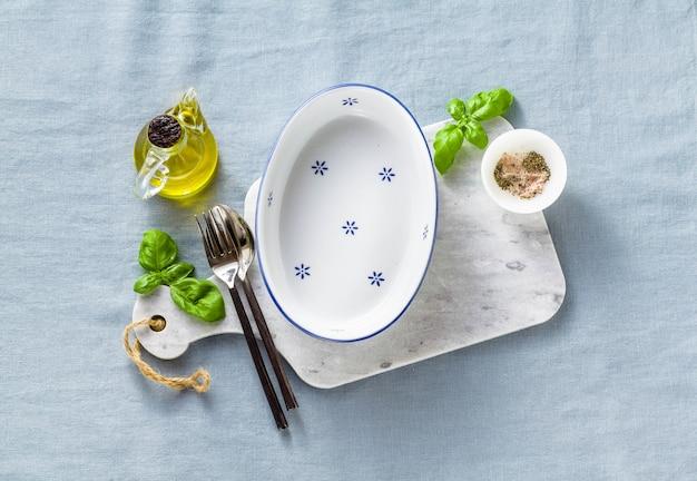 Plat de cuisson blanc en céramique vide sur une planche à découper en marbre et couverts sur une nappe en lin bleu avec de l'huile d'olive, des épices et des feuilles de basilic.
