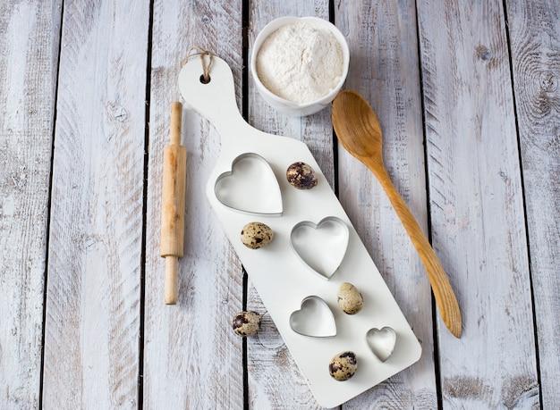 Sur un plat de cuisson en bois blanc en forme de coeur, oeuf et farine