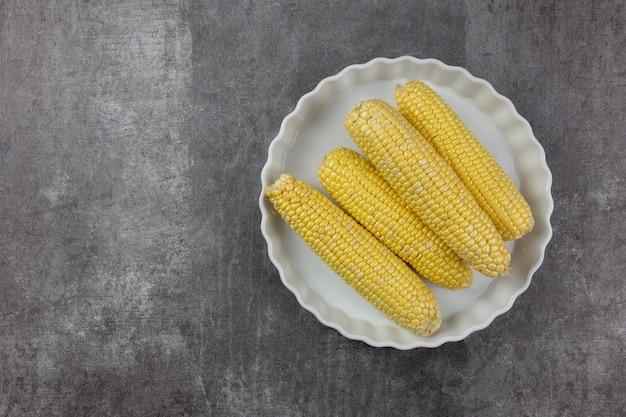Plat de cuisson en céramique blanche sur fond sombre avec du maïs, des légumes d'automne.