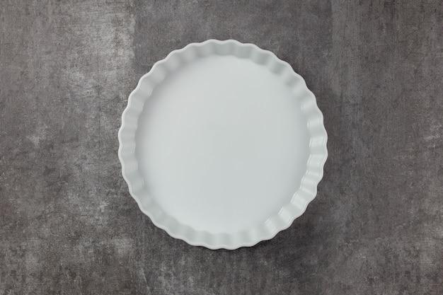 Plat de cuisson en céramique blanche sur fond sombre. fond de cuisson des aliments dans un four pour votre texte.