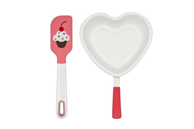 Plat de cuisson en céramique en forme de coeur blanc plat de cuisson et spatule rose sur blanc