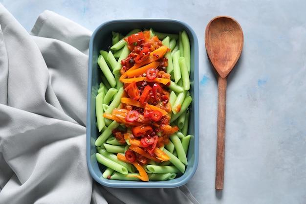 Plat de cuisson avec de savoureuses pâtes vertes sur une surface de couleur
