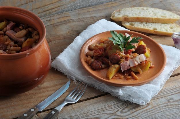Plat cuit dans un pot avec des pommes de terre, haricots, fumé dans un pot en argile