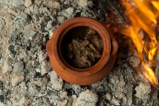 Un plat dans un pot en argile est préparé sur des charbons ardents. le plat est cuit et fumé au charbon de bois