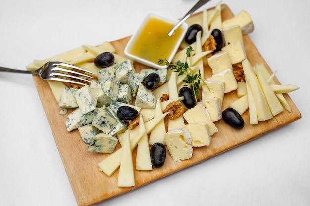 Plat de dégustation de fromages sur une assiette en bois.