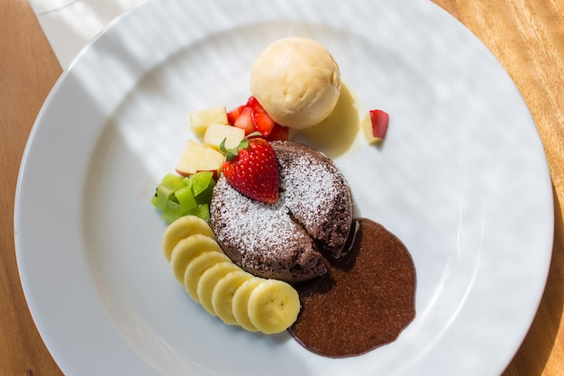 Un plat de dessert appelé lave au chocolat comprend de la crème glacée à la vanille, du kiwi et de la pomme
