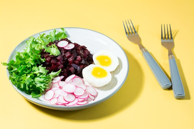 Un plat diététique à base de légumes. tartare de betterave, radis, salade de frise et œuf dur sur une assiette et une fourchette sur une table jaune. lumière forte