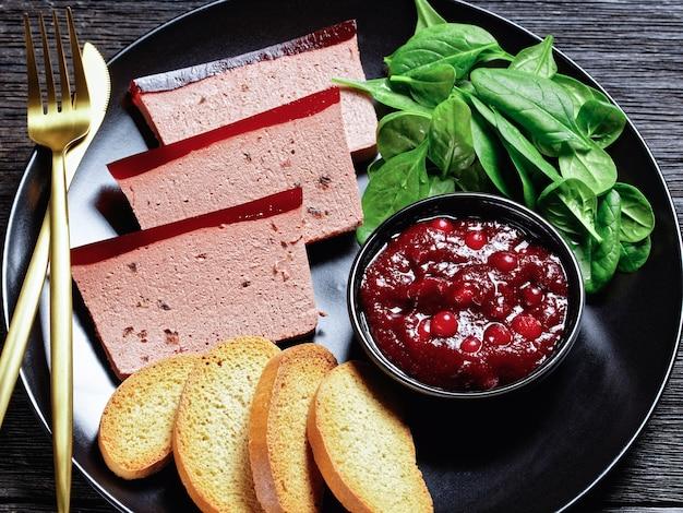 Plat français pâté de foie de canard avec marmelade de canneberges sur le dessus servi sur une assiette noire avec sauce aux canneberges, épinards et croûtons briochés, avec des couverts dorés sur une table en bois sombre, gros plan, vue de dessus