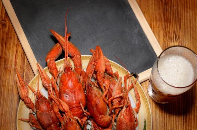 Plat de fruits de mer avec écrevisses bouillies rouges, tableau noir et bière