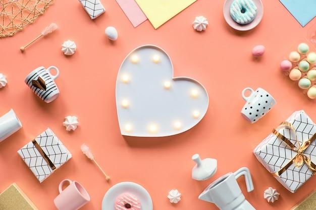 Plat géométrique de printemps posé en blanc et vert sur le mur rose pâques, fête des mères, anniversaire de printemps ou anniversaire. panneau chauffant en plastique, oeufs de pâques, cafetière, tasses, tulipes, cadeaux.