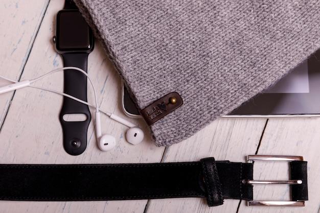Plat d'hiver avec smartwatch, tablette, chapeau tricoté et ceinture sur une table en bois rustique blanche. fond de noël et nouvel an.